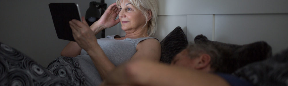 woman on tablet in bed