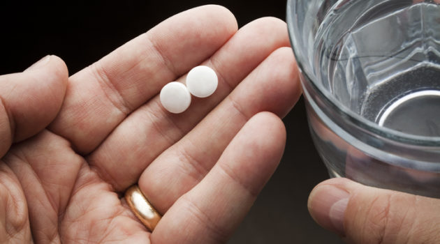 hands holding aspirin and water